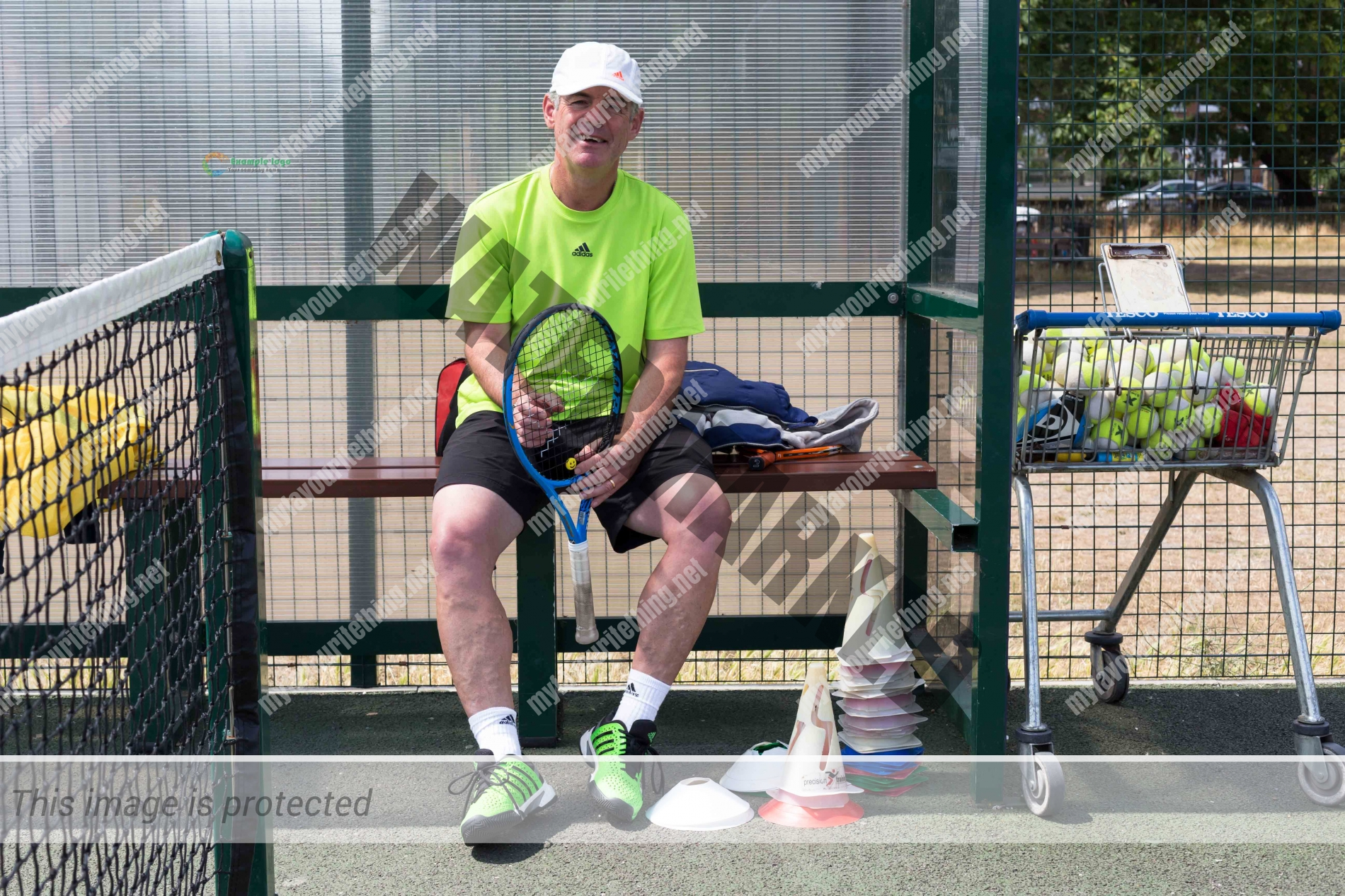 Tennis coach, Julian Cousins sitting on a bench at a tennis court holding a racket