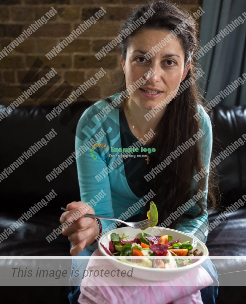 Engaging portrait of a woman holding a fork and a bowl of salad