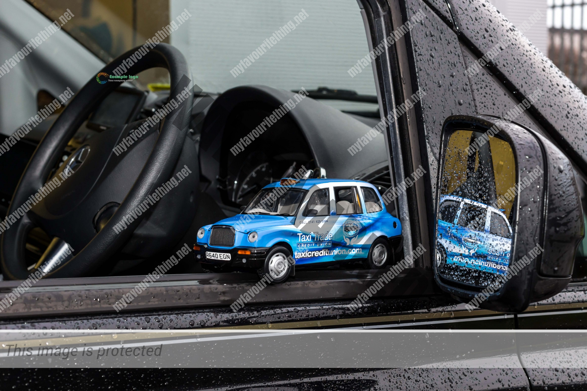Taxi Trade Credit Union model taxi sitting on the window of a Glasgow taxi